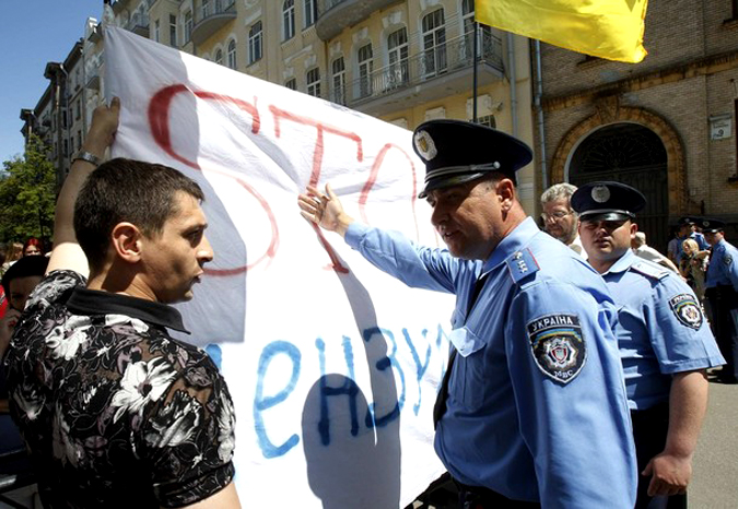 "A journalist (L) argues with police holding a poster with a sign ""Stop Censorship!"" during a demonstration in central Kiev"